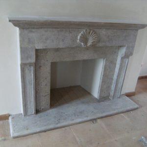 Caminetto geometrico con motivo classico a conchiglia in pietra